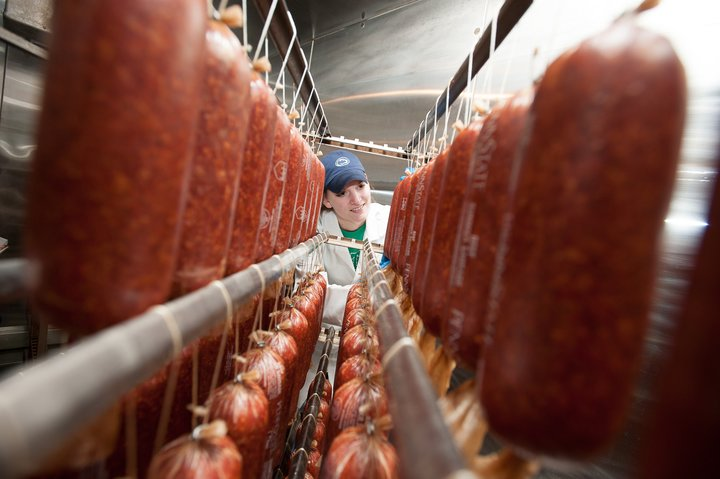 Person Standing Between Rows of Packaged Meat